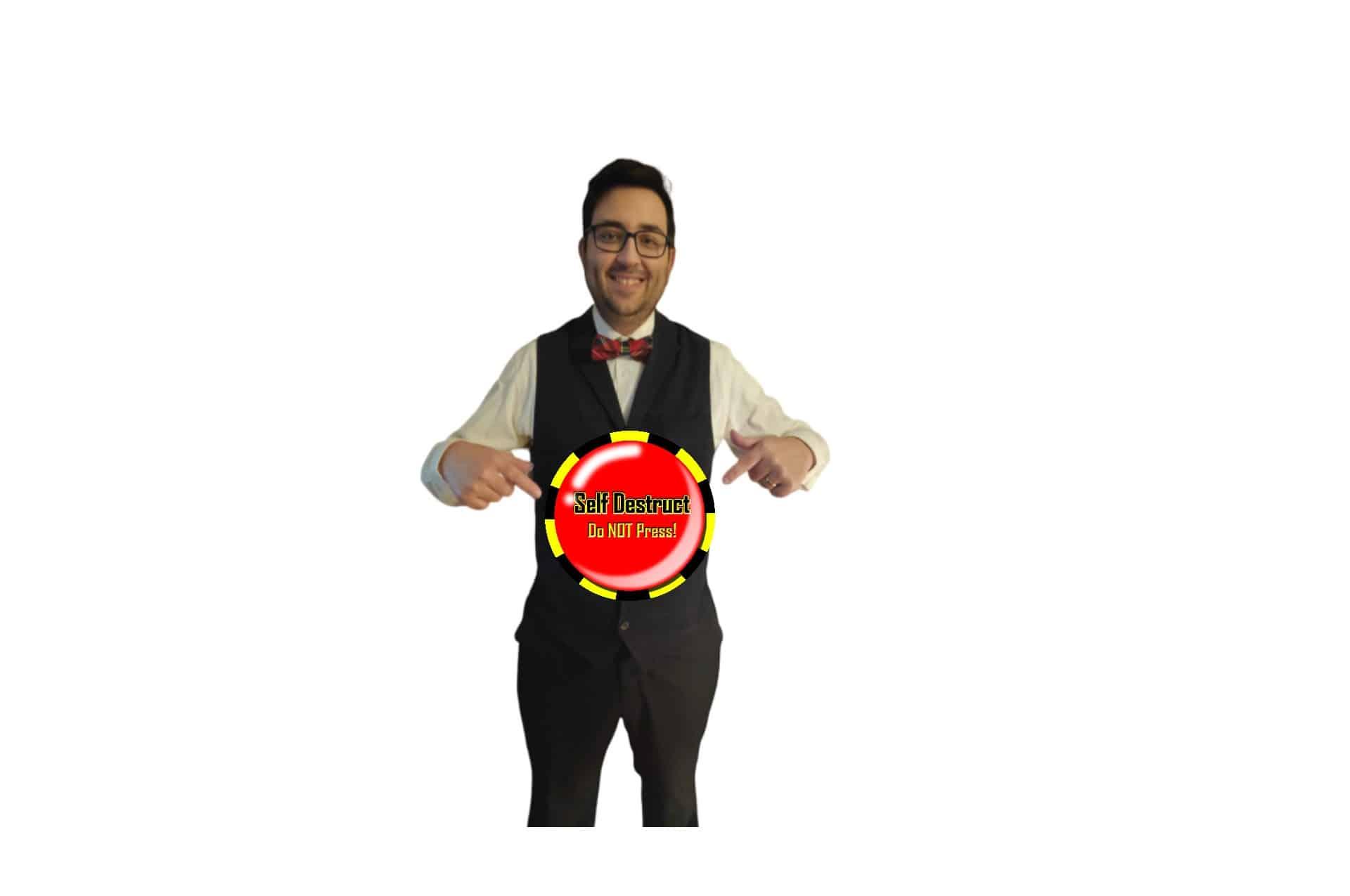 """Professor M com um botão com """"Self destruct do not press"""" escrito, serve como imagem de sobreposição do vídeo da página sobre mim"""